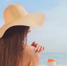 Sunbather-Putting Sunscreen on Her Shoulder Wearing Big Tan Sun Hat